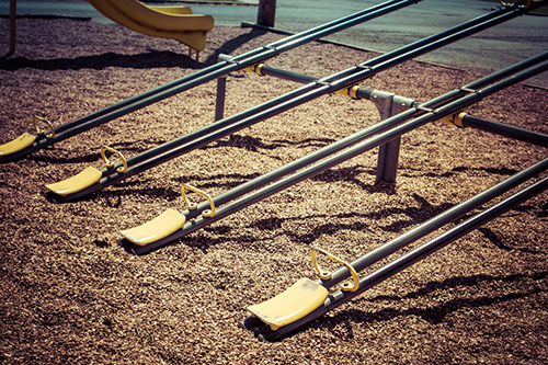 Four seesaws in a group, with yellow seats in a park with the ground made out of mulch,