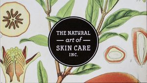 Business card with a decorative fruit and floral pattern and a black and white circle in the middle that advertises for a skin care company.