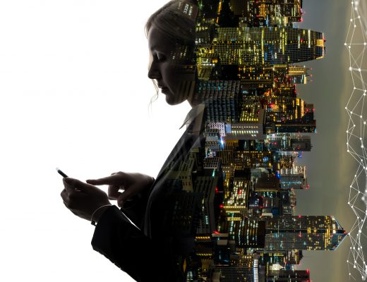 Attractive woman in business clothes types on her phone and leans against a city at night that has been inverted by 90 degrees.