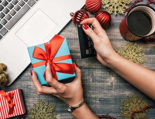 Workspace with laptop, red cup on wooden background. Baubles, garland, tree ornaments, gift box. Woman hand holding a credit card