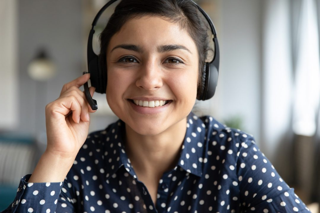 Smiling indian girl teacher counselor telesales agent wear wireless headset look at camera webcam, distance teaching, customer support service concept, telemarketing professional closeup portrait